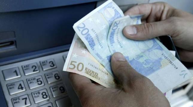 Un hombre sacando dinero de un cajero automático.