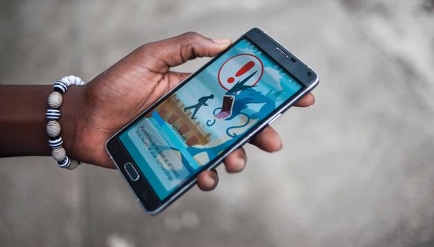 Un joven abriendo la 'app' Pokémon Go.