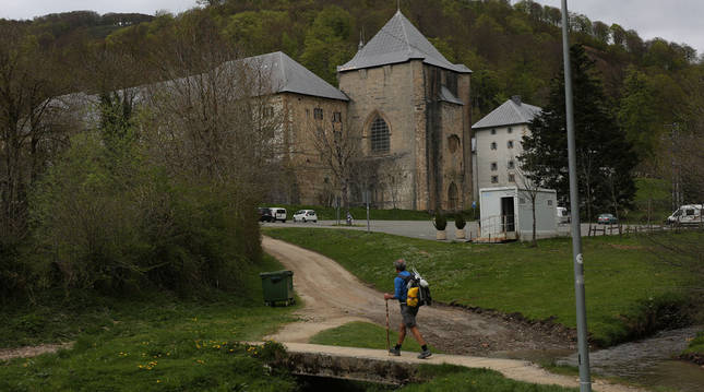 Foto de un peregrino caminando hacia la colegiata de Roncesvalles.