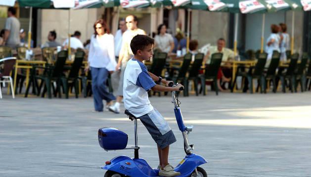 Un niño pasea en un patinete con motor.