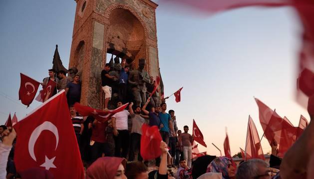 Turcos ondean banderas junto a una estatua del fundador de la Turquía moderna, Mustafa Kemal Ataturk, en Estambul.