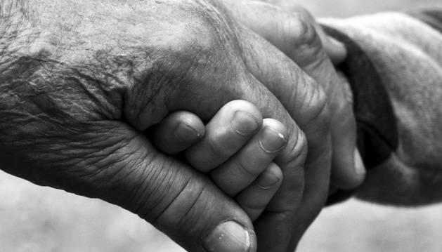 Dos ancianos se dan la mano.