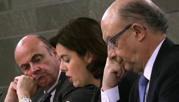 La vicepresidenta del Gobierno, Soraya Sáenz de Santamaría, acompañada por los ministros de Economía y Competitividad y de Hacienda, Luis de Guindos (i) y Cristóbal Montoro.