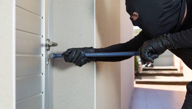 Un encapuchado trata de abrir una puerta con cerradura mediante una palanca.