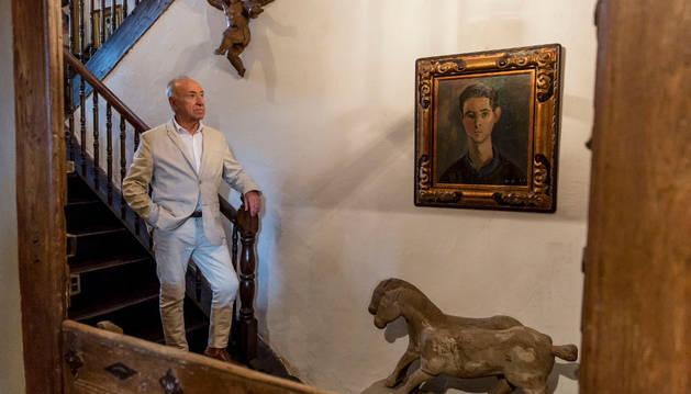 Jesús Montes en la escalera de Karakoetxea, ante el retrato que le hizo Menchu Gal cuando tenía 18 años y unos caballos etruscos.