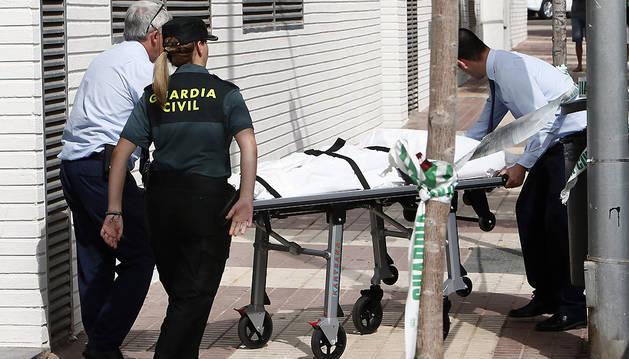 Trabajadores de los servicios funerarios trasladan el cadáver de la mujer fallecida en Benicassim.