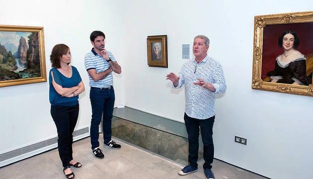El concejal de Cultura del Ayuntamiento de Tudela, Javier Gómez Vidal (dcha.), explica a la consejera Ana Herrera y a Eneko Larrarte el contenido de la exposición.