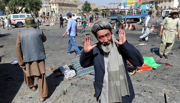 Un hombre de la minoría hazara lamenta el ataque, con alguna de las víctimas detrás.