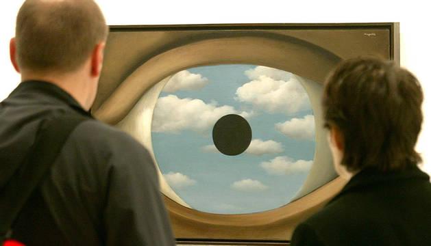 Dos personas observan una obra de Magritte.