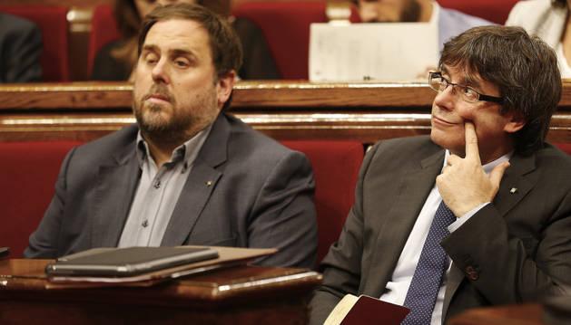 El presidente de la Generalitat Carles Puigdemont (d) y el vicepresidente, Oriol Junqueras (i), durante la sesión de control en el Parlament de Cataluña.