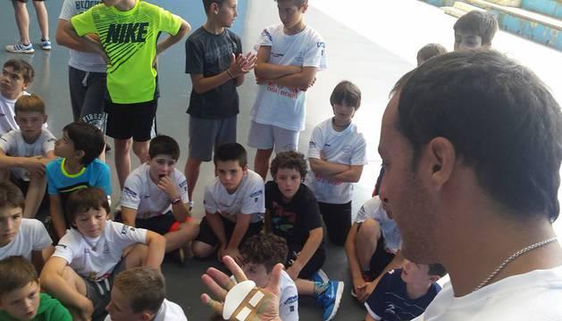 Irujo, enseñando a un grupo de chicos cómo colocarse los tacos.