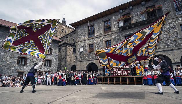 Julio Beretens Tapia (izda.) con la bandera de Isaba y Haritz Jamar Lusarreta (dcha.) con la del Roncal bailando en la plaza de la Constitución.