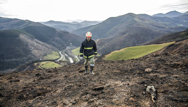 El voluntario del parque de bomberos de Lesaka José Antonio Sola Gómara, sobre una de las franjas quemadas en el monte Frain.