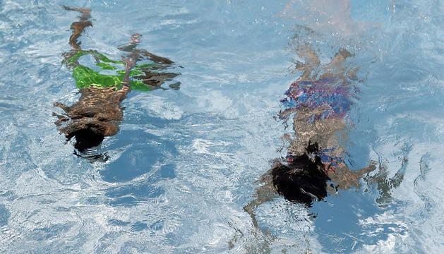 Dos personas se refrescan en el interior de una piscina en Madrid.