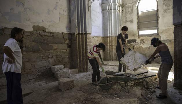 Tres voluntarios retiran escombros ante la mirada del director, Juanjo Bienes, a la izda.