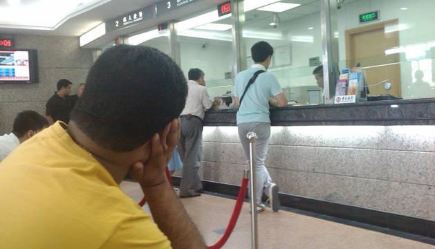 Varias personas esperan en la ventanilla de un banco.