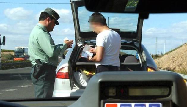 Un miembro de la Guardia Civil de Trafico pone una multa a un conductor por exceso de velocidad.