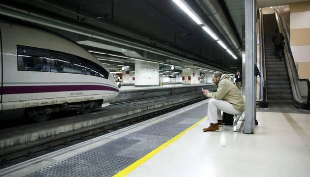 Un pasajero espera sentado a su tren en la estación de Sants, en Barcelona.