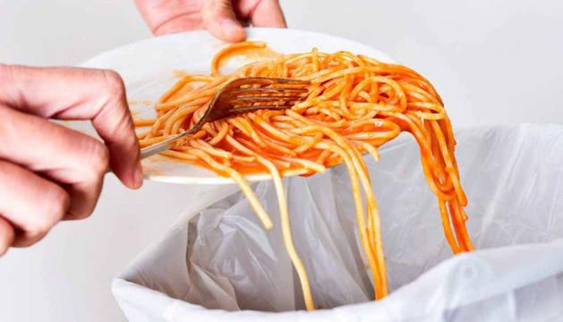 Una persona tira al cubo de la mesa las obras de un plato de espaguetis con tomate.