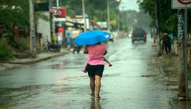 Habitantes del municipio de Tzubcacab, en el estado mexicano de Yucatán, circulan por las calles afectadas tras el paso de la tormenta tropical Earll.