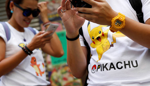 Dos personas juegan a Pokémon Go en Hong Kong, China.