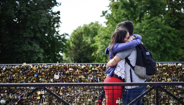 Una pareja de enamorados se abraza en un puente parisino.
