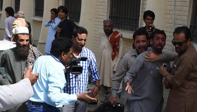 Abogados y agentes de seguridad se reúnen alrededor de los cuerpos de las víctimas de la explosión.