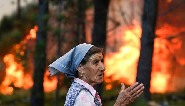 Una mujer, junto al fuego en Carvalheda, en el Valle de Cambra de Portugal.