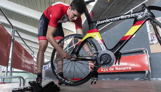 Juan Peralta ajusta la cadena de su bicicleta antes de una sesión de entrenamiento en el Velódromo Miguel Induráin  de Tafalla.