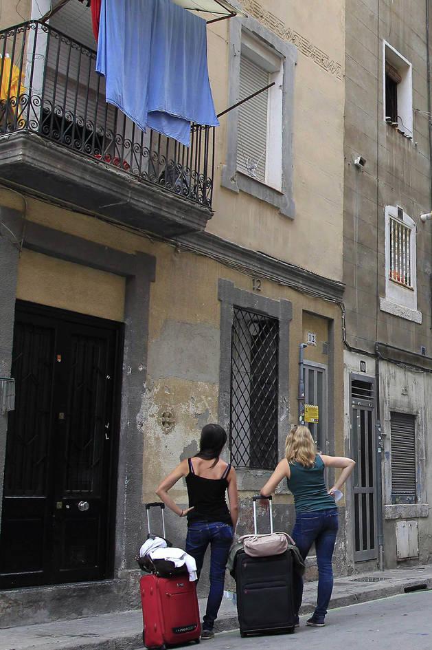 Dos turistas esperan para acceder a su apartamento turístico en Barcelona.