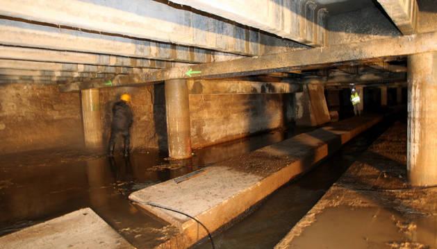 Dos operarios trabajan en la reparación del cubrimiento del Queiles cerca del paseo del Prado, donde desemboca el río.