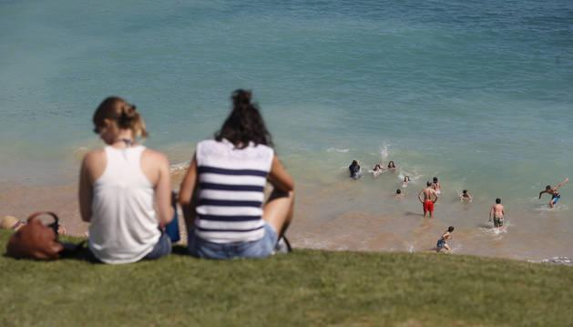 Dos jóvenes observan a un grupo de amigos bañándose en una playa.