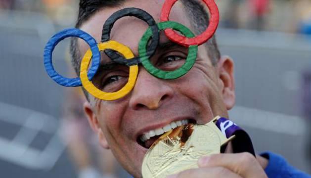 Un hombre simula morder una medalla de oro.