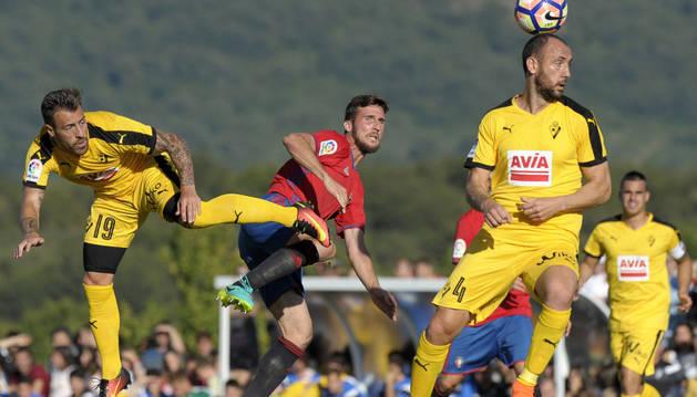 El defensa de Osasuna Oier Sanjurjo (d) lucha por un balón ante los defensas Iván Ramis (d) y Antonio Luna (i), del Eibar, durante el partido amistoso.