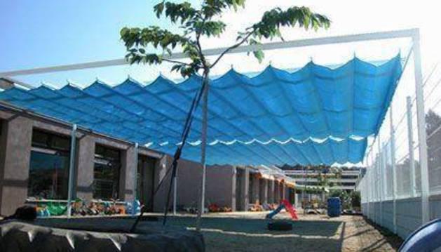 Los toldos colocados en el patio exterior de la escuela infantil para proteger el espacio del sol.