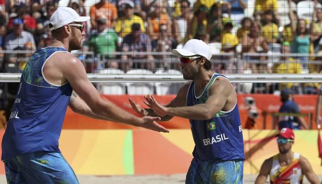 La pareja brasileña celebra un punto del partido.