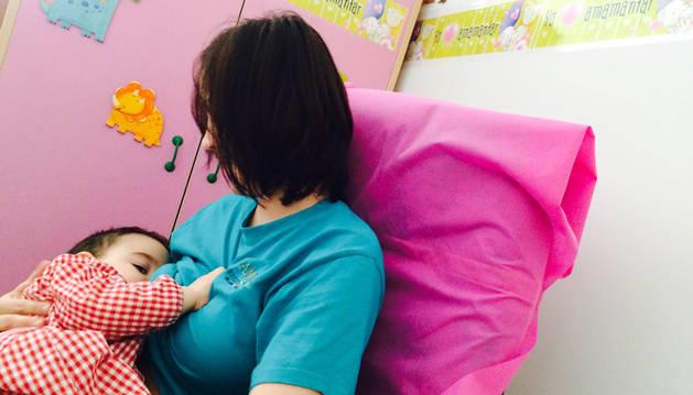 Una madre dando el pecho a su hijo.
