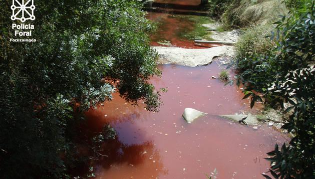 Río Juslapeña teñido de rojo en Orcoyen.