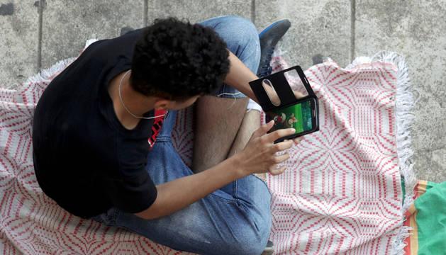 Un joven juega a Pokémon Go en un parque.