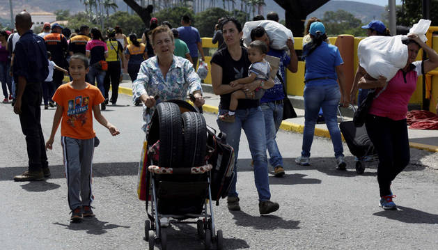 Varios venezolanos cruzando a su país por el puente internacional Simón Bolívar tras hacer compras en Cúcuta, Colombia.