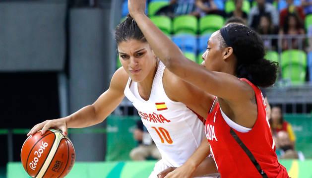 . La jugadora de la selección española de baloncesto Marta Xargay (i) se dirige a la cesta ante Nayo Raincock (d) de Canadá.