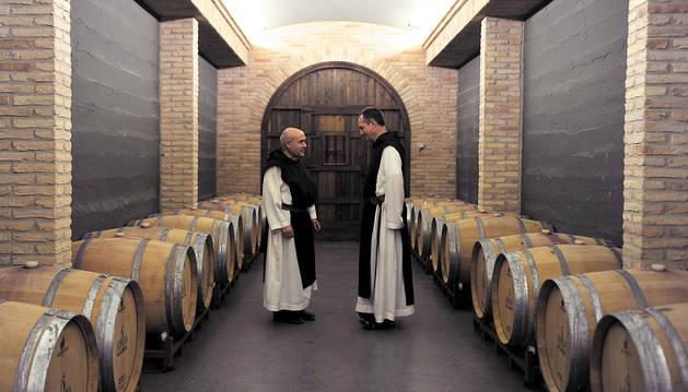 El hermano Daniel Gutiérrez Vesga (izda.) y el abad Isaac Totorika Izagirre (dcha.) en la bodega del monasterio rodeados por algunas de las barricas que se subastarán este viernes.