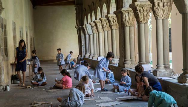 Los 15 niños participantes en el taller realizan sus maquetas en el claustro de la catedral con las dos monitoras del taller.