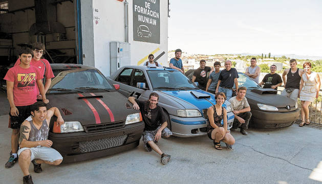 Imagen de los alumnos que han completado el curso del Servicio Navarro de Empleo con los coches que han construido.