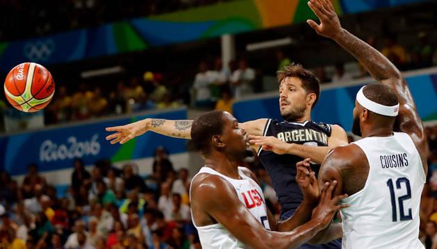 Kevin Durant (i) y DeMarcus Cousins de Estados Unidos disputan el balón contra Nicolas Laprovittola (c) de Argentina.
