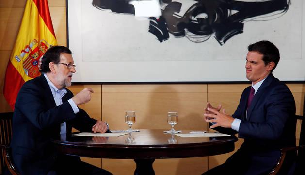 El presidente del Gobierno en funciones, Mariano Rajoy (i), y el líder de Ciudadanos, Albert Rivera (d), conversan durante la reunión que han mantenido en el Congreso.