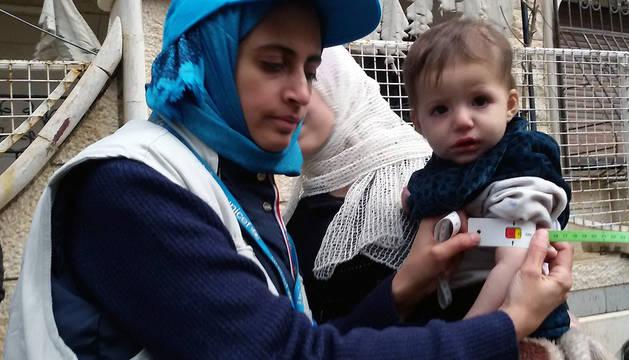 Una trabajadora de UNICEF atiene a un niño en la ciudad siria de Madaya.