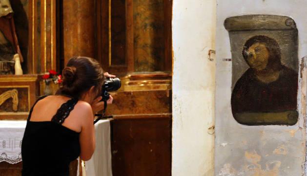 Una turista fotografía la obra de arte restaurada por al vecina de Borja.