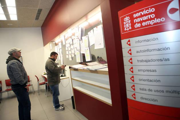 Dos desempleados consultan las ofertas de trabajo expuestas en una oficina de empleo.