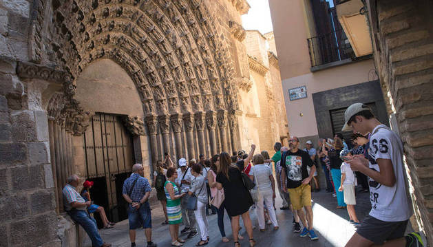 Varias personas admiran y fotografían la Puerta del Juicio de la Catedral de Tudela, antes de una visita guiada a la misma.